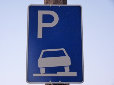 Sign showing car partially on the street and partially on the sidewalk