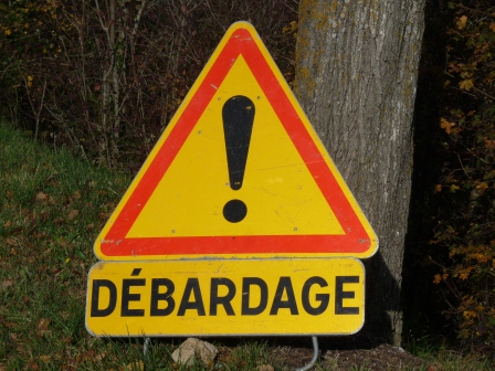 "Standard warning sign with exclamation point and unknown description of hazard below ""Debardage"""