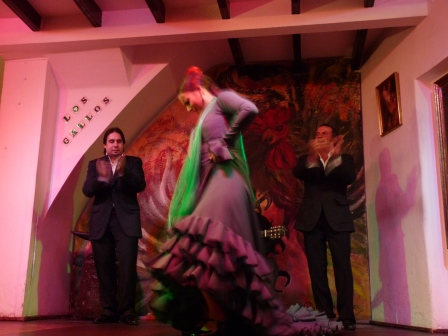Flamenco dancer in green dress on stage with singers in background