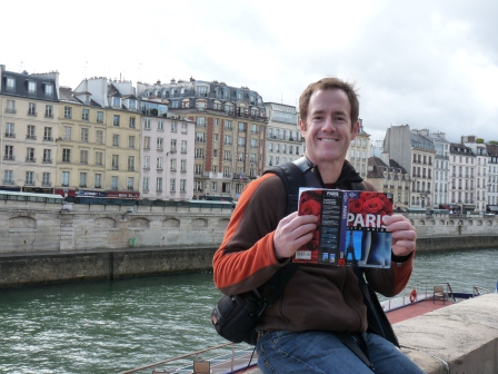Patrick with a Paris guidebook on the riverbank with the left bank in the background