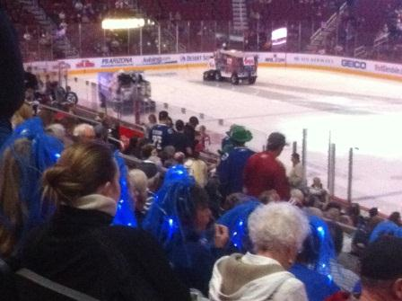 Canucks fans with blue hair in their seats at the game