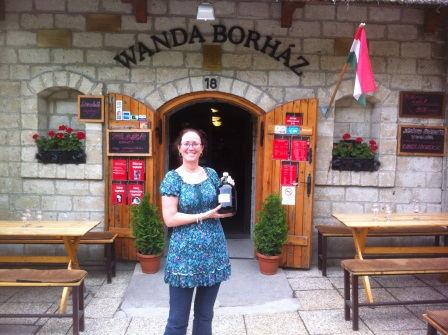 Diane standing with 2 Litre green jug of wine in front of Wanda's wine cellar