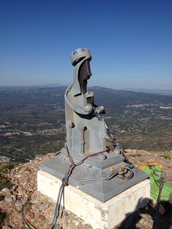Metal status of Madonna with child on concrete base on the summit
