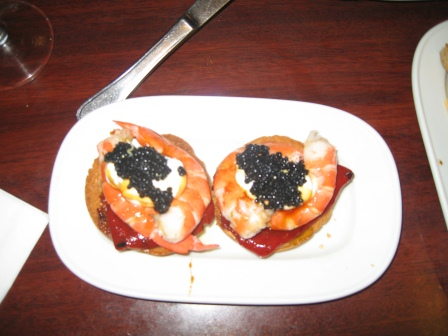 Two tapas on white plate with sun-dried tomatoes, shrimp, and caviar