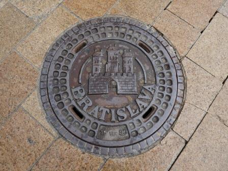 "Manhole cover with picture of castle and ""Bratislava"" surrounded by brown tile"