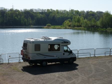 Camper van sitting in front of the reservoir in a gravel lot