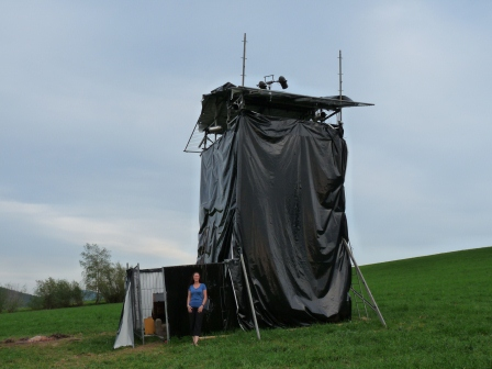 A tower made of scaffolding and plastic in the field near the witch pyre
