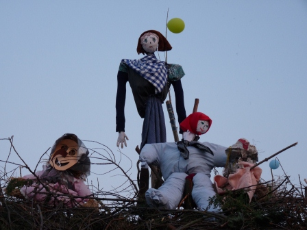 A 'witch' made of wood and fabric on top of the wood pile