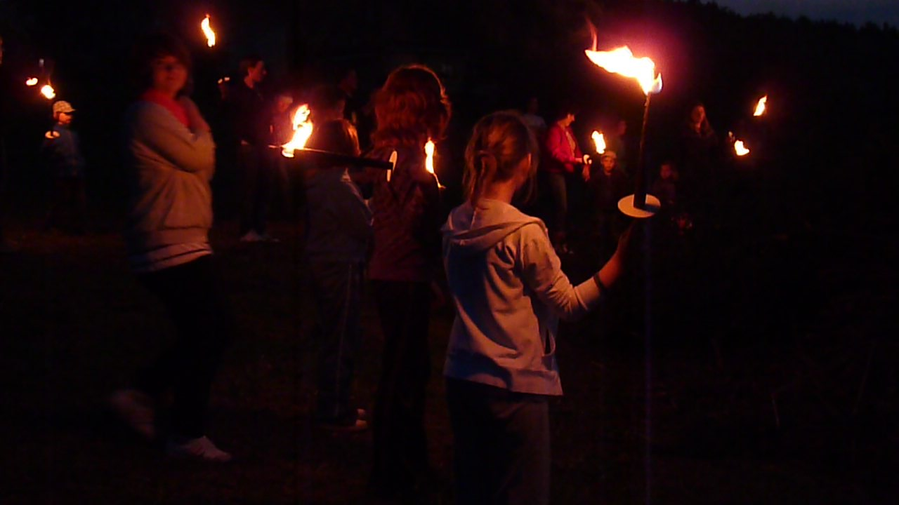 Children in the dark carrying burning torches