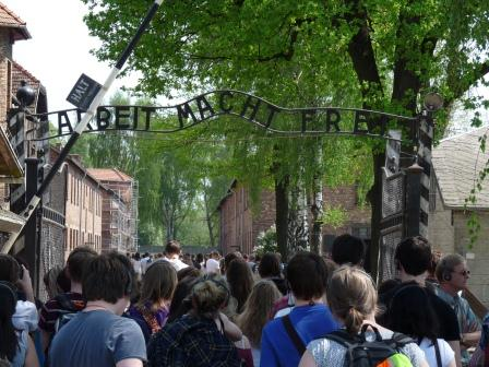 Many visitors passing through gate with words 'Arbeit Macht Frei' (Work will make you free) above