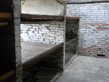 Two wooden bunks each with 3 levels with concrete floor and brick walls