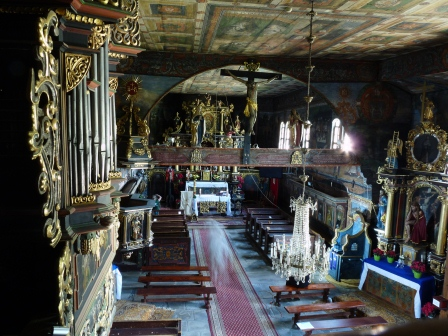 Photo taken from rear balcony of a church with a carved wood interior that is hand painted