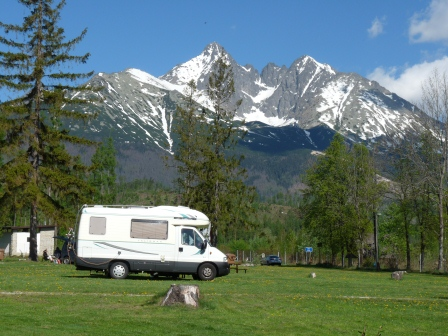 Our camper van parked in a grassy field with tall, snowcapped mountains behind