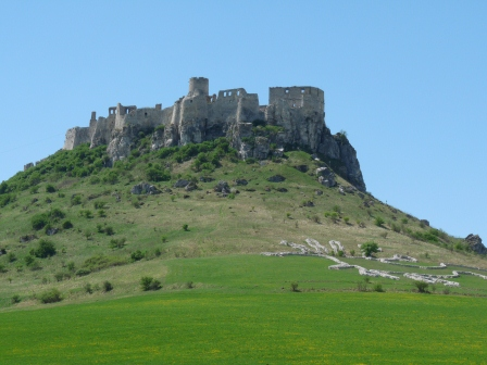 Ruins of a castle on a hill with grassy fields in the foreground