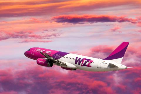 Hot pink, purple, and white plane flying through purple clouds