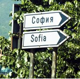 Two black and white signs pointing to Bulgaria's capital city Sohpia, the top one in Cryrillic and the bottom one in Latin charactes