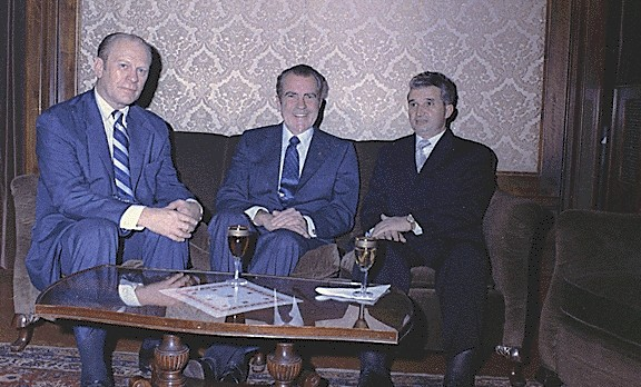 Ceauşescu in black suit seated on couch beside Geral Ford and Richard Nixon (both wearing blue suits), coffee table in front