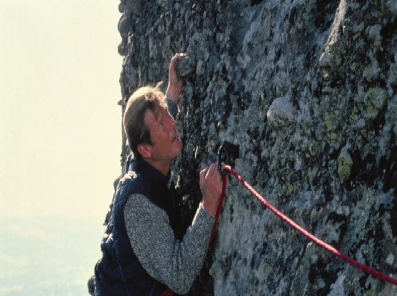Roger Moore climbing Meteora tower as James Bond