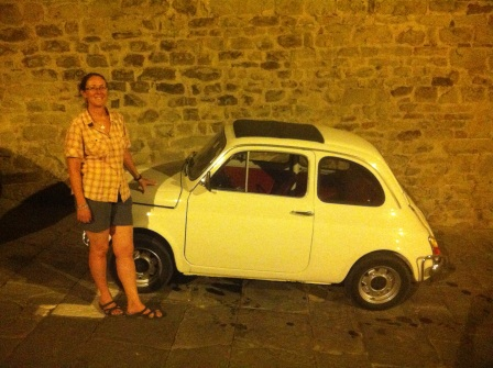 Diane standing beside a tiny yellow car an night witha brick wall behind