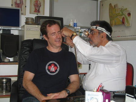 Greek doctor in white shirt wearing a head lamp cleaning my ear.