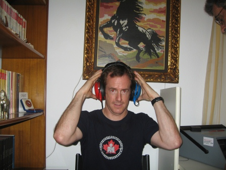 Patrick wearing large headphones, one red one green and holding the sides of his head