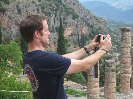 Patrick taking a picture of some Greek ruins holding the carmera with outstreched arms