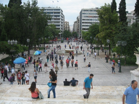 View from the top of steps overlooking square filled with normal people going about their business