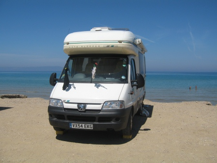Our white motor home parked on the beach facing toward the camera with blue water and sky in the background