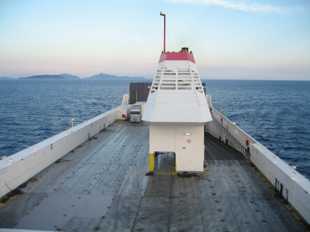 Empty grey deck on a ship with white railing and tower, with ocean and sunset in the background