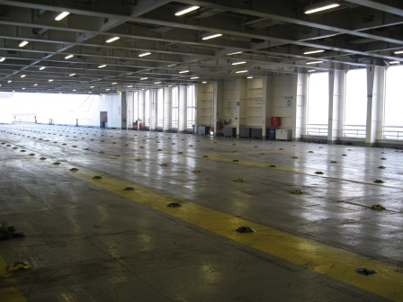 An empty metal deck on a deserted ferry.  Covered with windows in the background.