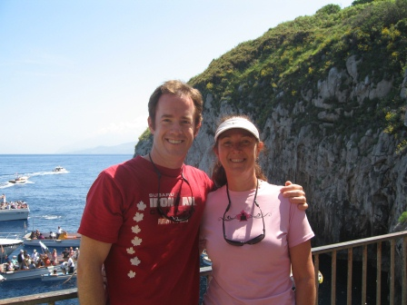 Diane in pink shirt and Patrick in red shirt with arm around her, with sea cliff, water, and boats in the background