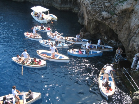 8 small white row boats pushing for entry into the Blue Grotto