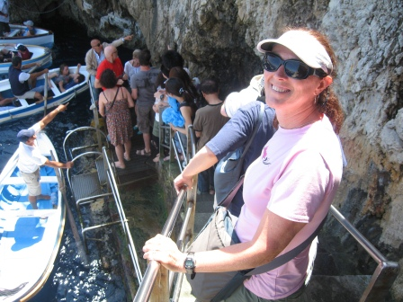 Diane in pink shirt and white visor waiting on steps with others below, and a white boat floating near the platform at the bottom