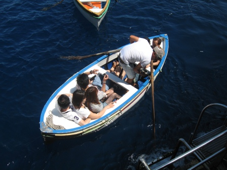 A small white row boat with standing pilot and 6 Asian people crammed in to it