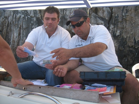 Two men in white shirts, one smoking, handling cash, on a small boat covered by a white awning