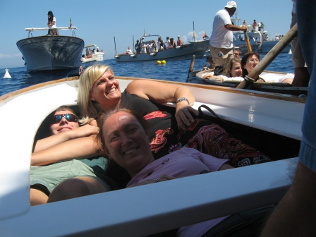 Diane and others laying prone in the bow of our roatbat with other boats in the background