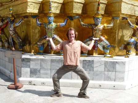 Patrick posing in an awkward pose to mimic the brightly coloured Thai statues in the background