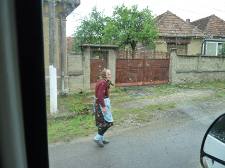 Romanian woman walking beside road wearing skirt and aprom