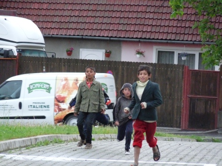 Three children running toward the car wearing pants and jackets