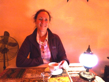 Diane seated at a table with small lamp, orange wall, with coffee in white cup