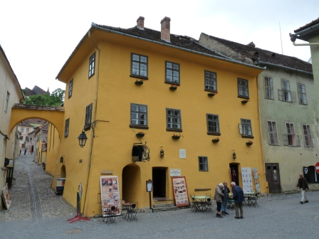 Three story corner house on main square painted golden yellow