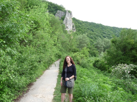 Diane beside a walking path with lush green grass and trees and a cliff in the distance