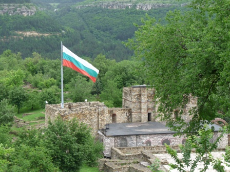 Ruined castle on hilltop surrounded by green trees.  Single flagpole with raised Bulgarian flag.