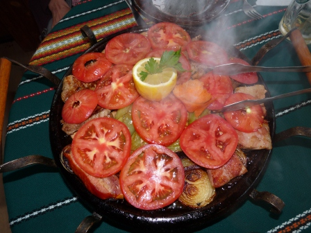 Hot circular metal pan covered with grilled pork, onions, tomatoes, and yellow peppers.