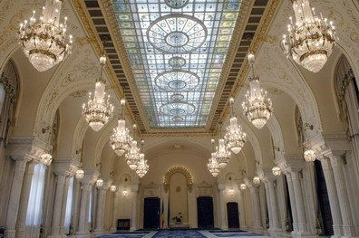 Huge white hall with giant skylight lined with columns and chandeliers