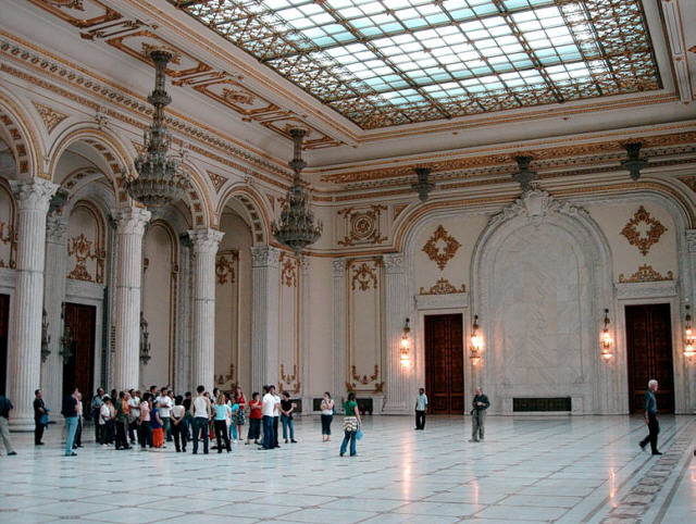 A huge hall with skylight, white floor, and people milling about