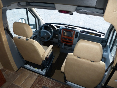 The cab from the rear with 2 seats, dash, steering wheel, and multi-media system