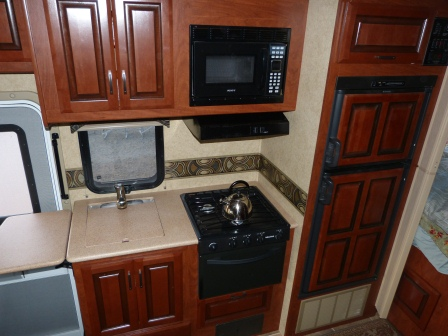 The kitchen with cupboards, cook top, oven, microwave, and fridge.