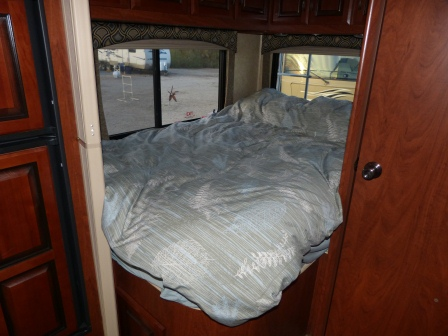 The bed with a comforter with windows on 2 sides