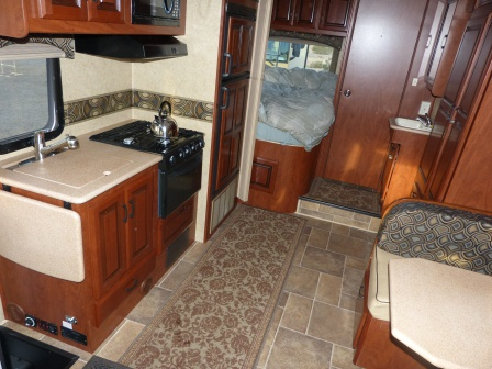 Kitchen on the left, bed and bathroom in the rear, storage and dinette on the right